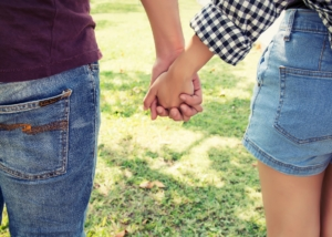 Young couple in love holding hands walking in the park.